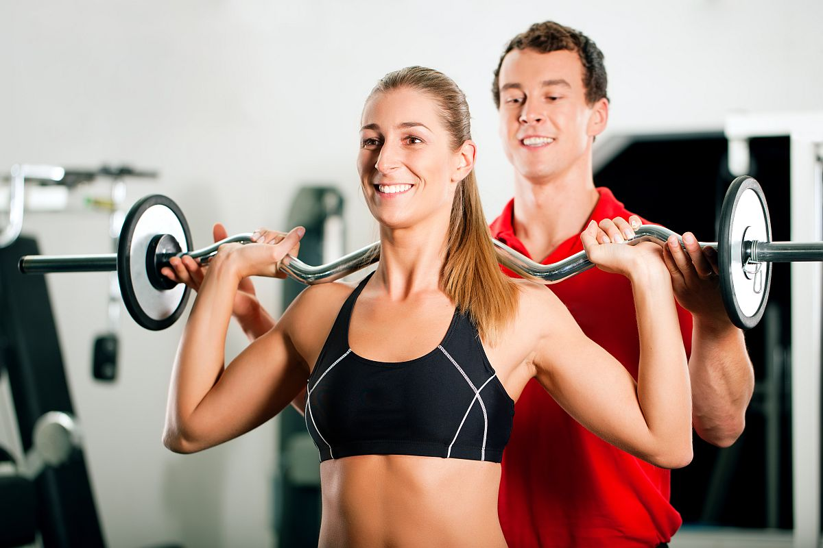 Woman in gym with personal fitness trainer exercising power gymn