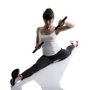 sport karate girl doing splits with nunchaku, fitness woman silhouette studio shot over white background