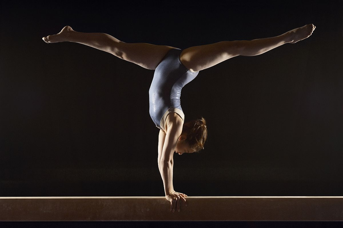 Side view of a female gymnast doing split handstand on balance b