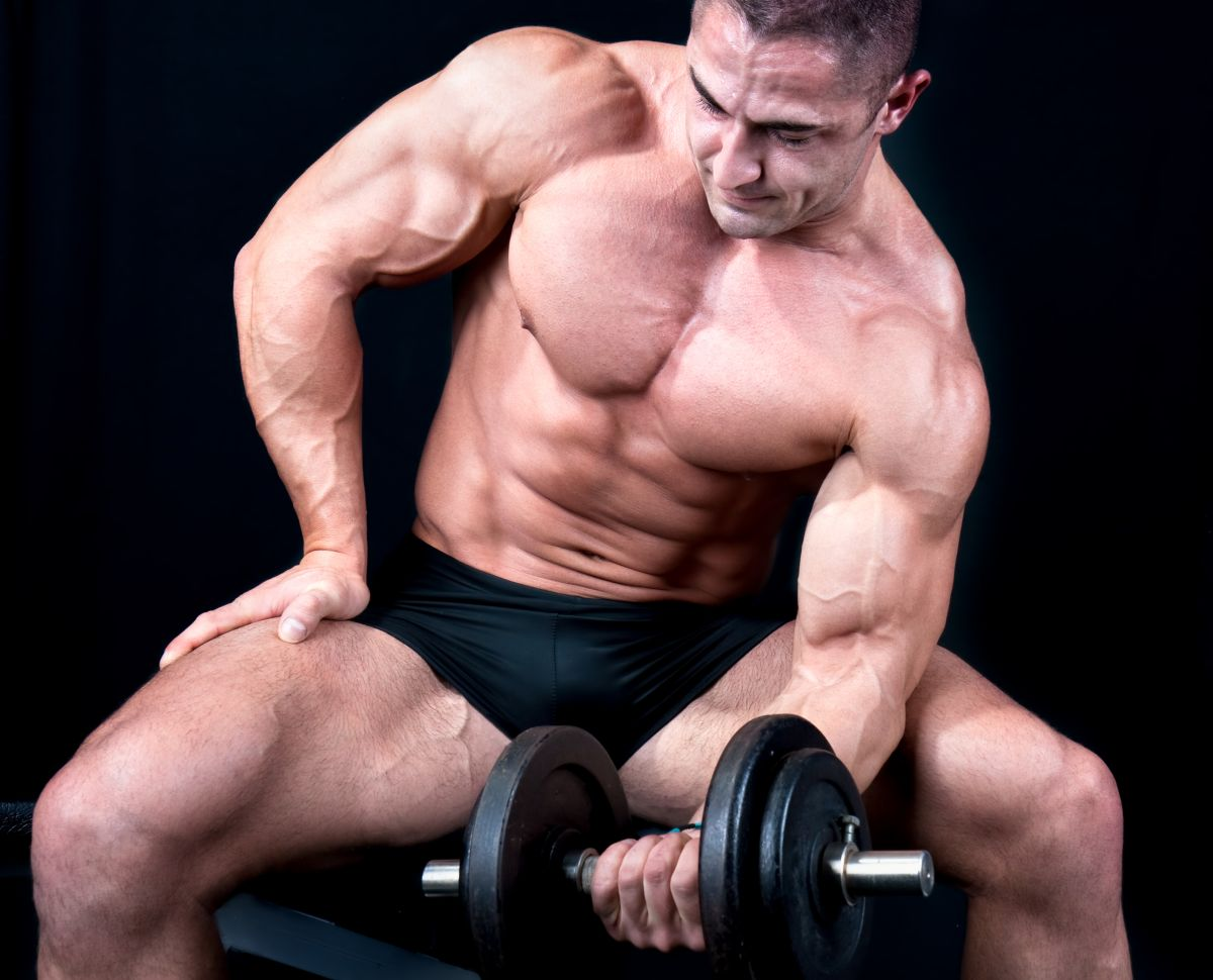 Man on bench with a bar weights in hands training, isolated on b