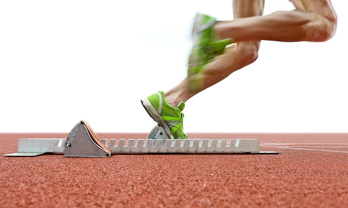 Action packed image of an athlete leaving the starting blocks fo