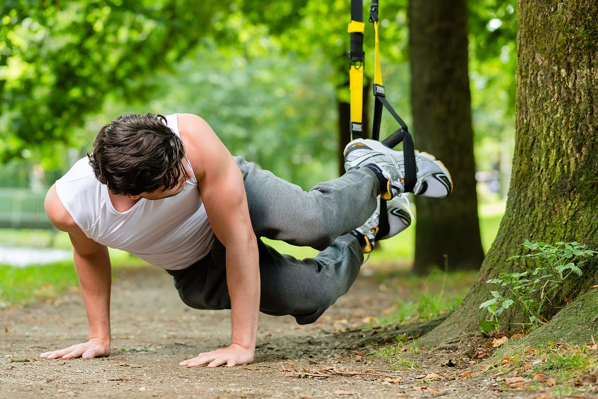 Young man exercising with suspension trainer sling in City Park