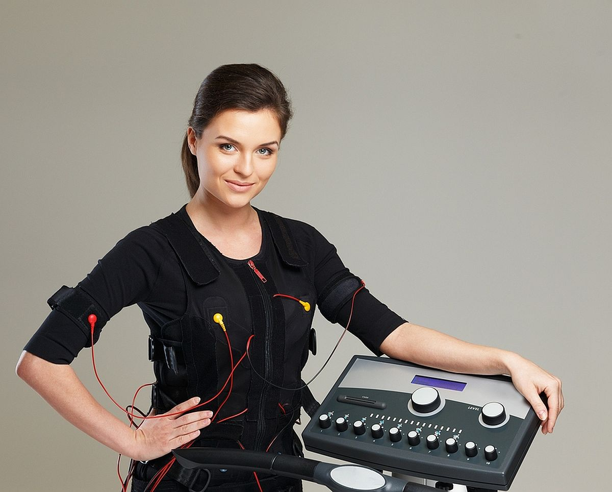 Young woman in training costume near Electro Muscular Stimulatio