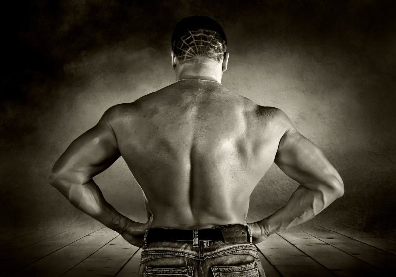 Bodybuilder posing on the outdoor grunge background