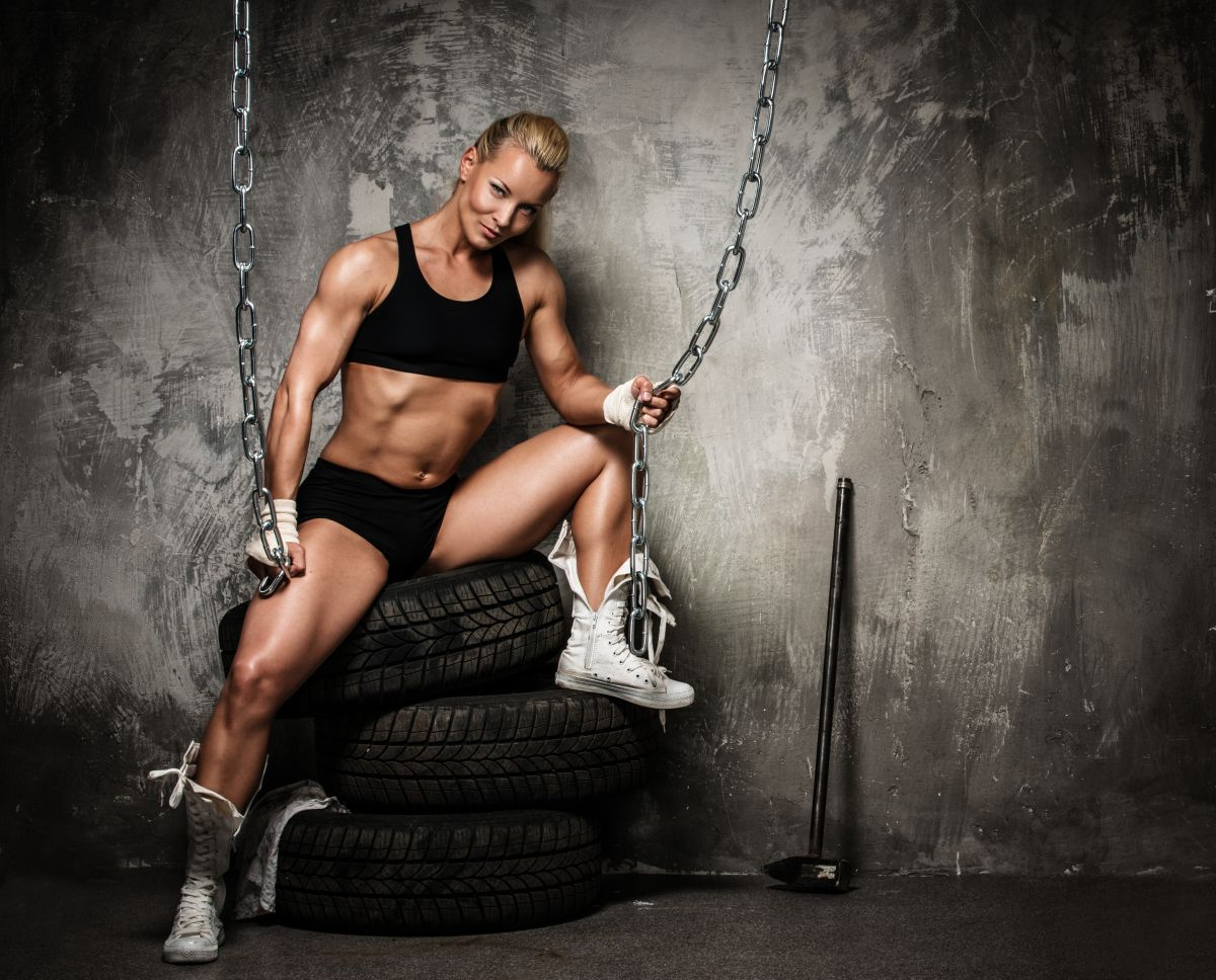 Beautiful muscular bodybuilder woman sitting on tyres and holdin