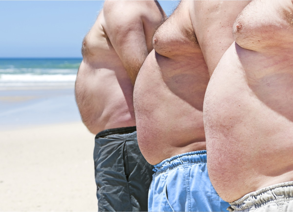 Close up of three obese fat men on the beach showing their unhea