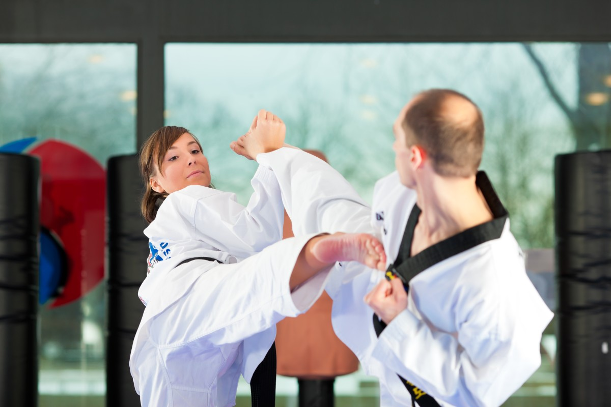 People in a gym in martial arts training exercising Taekwondo, b