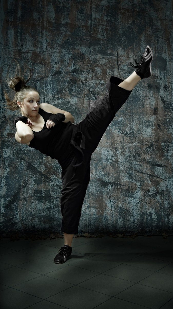Portrait of young woman practice martial arts – high kick