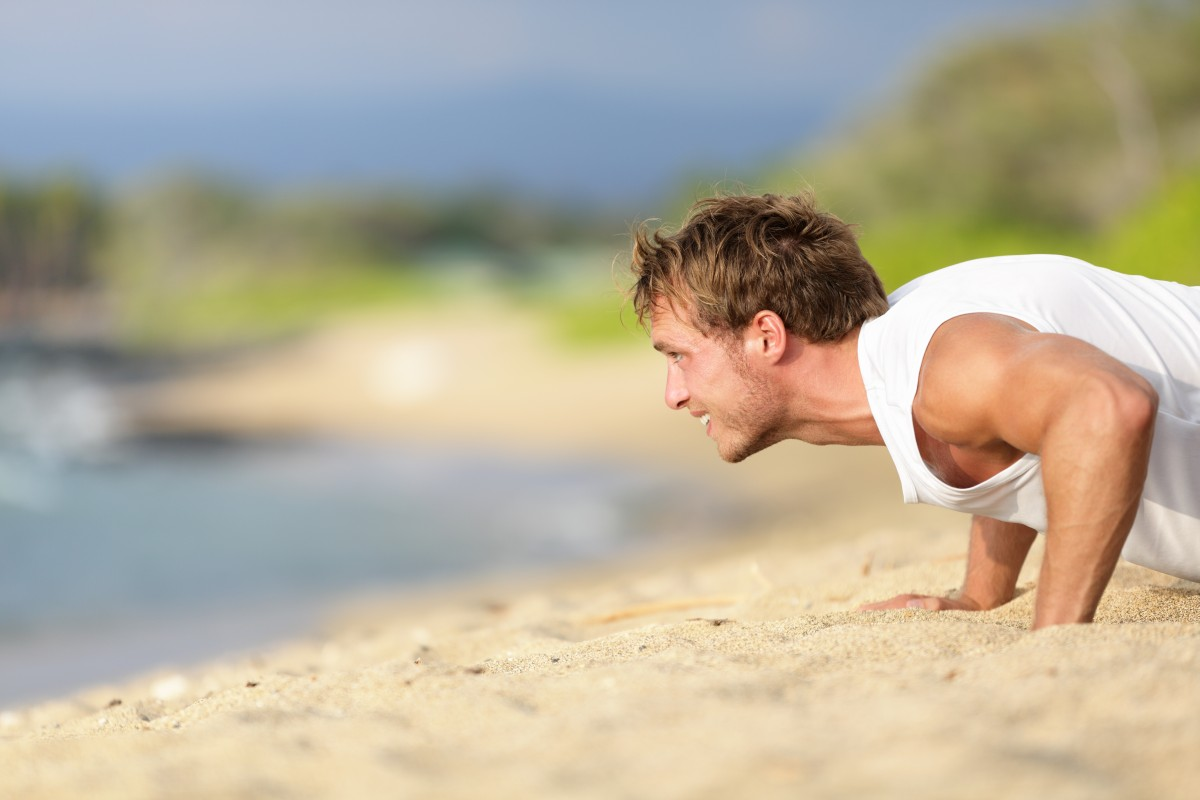 Push-ups – man fitness model training pushups on beach outdoors.
