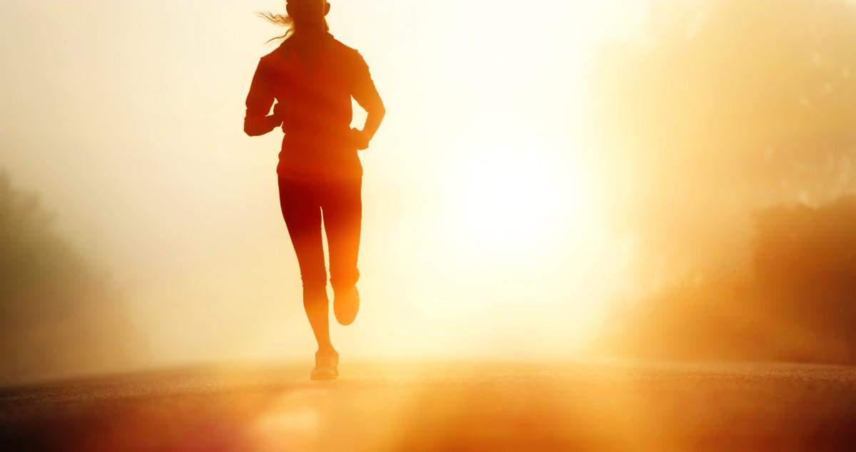 Runner athlete feet running on road. woman fitness silhouette su
