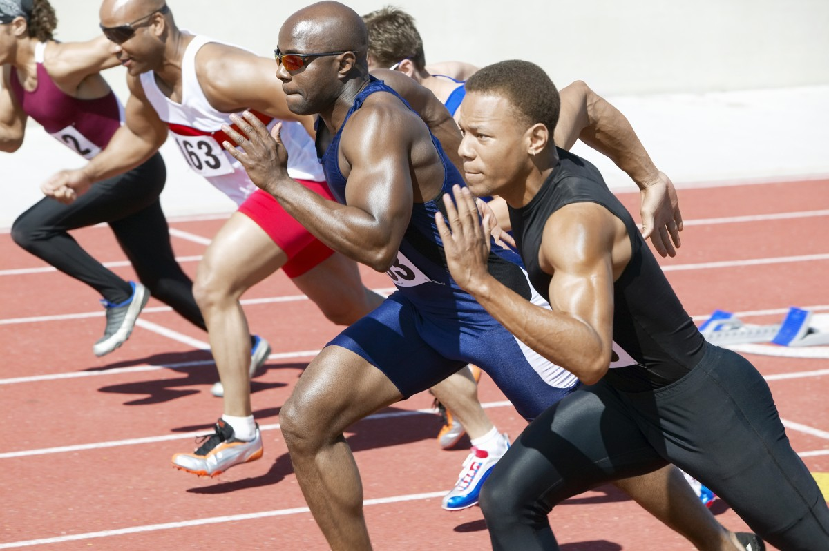 Side view of multiethnic male athletics sprinting on running tra