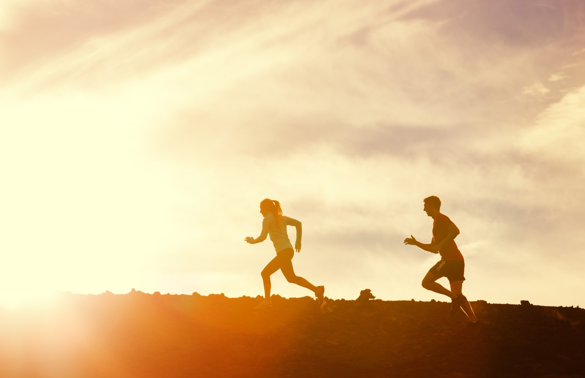 Silhouette of Man and woman running together into sunset, Wellne